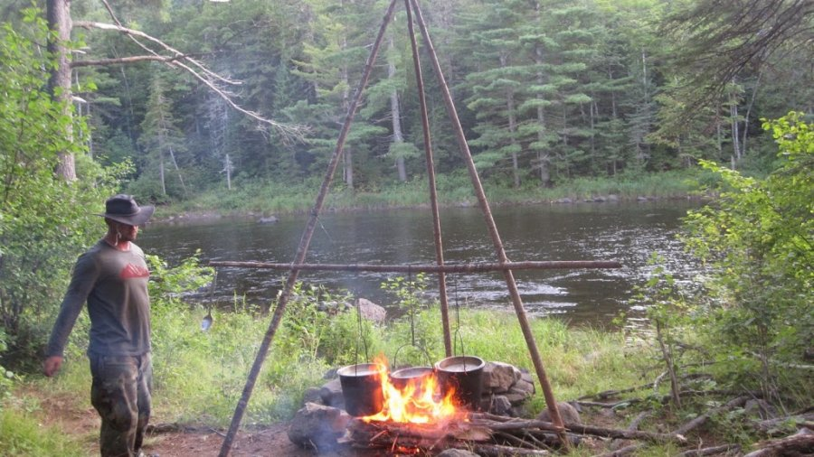 Cooking dinner on the East Branch of the Penobscot.  Tripod with a galley pole. …