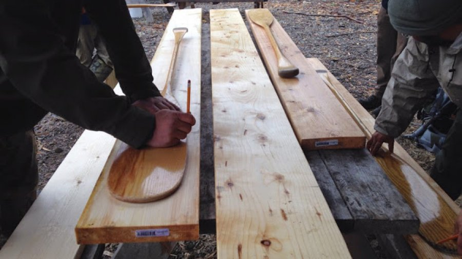 Beginning the canoe paddle-making process: tracing a blade onto a paddle blank