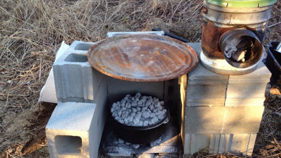 Windy and rainy lately, so we made a windbreak/raincoat for dutch oven cooking out of blocks and a barrel lid