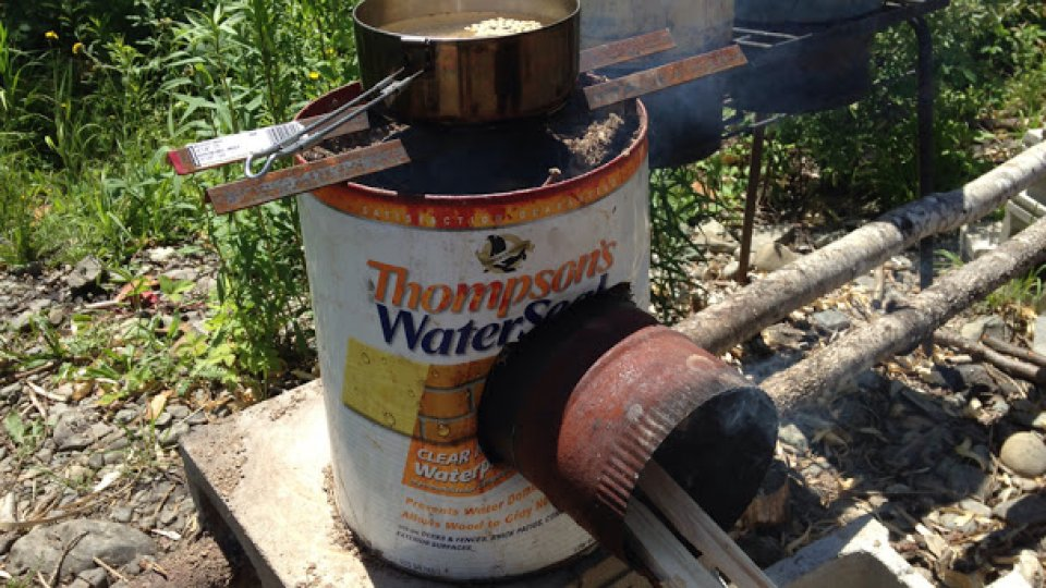 15 minutes later, some dirt and a piece of angle iron cut in half, and the new rocket stove is cooking lunch