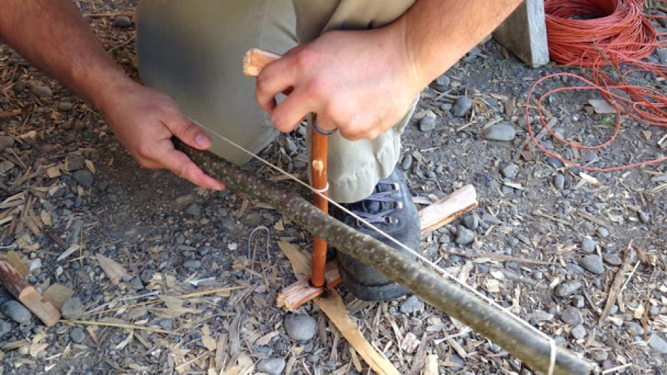 Fire by friction with a bow drill