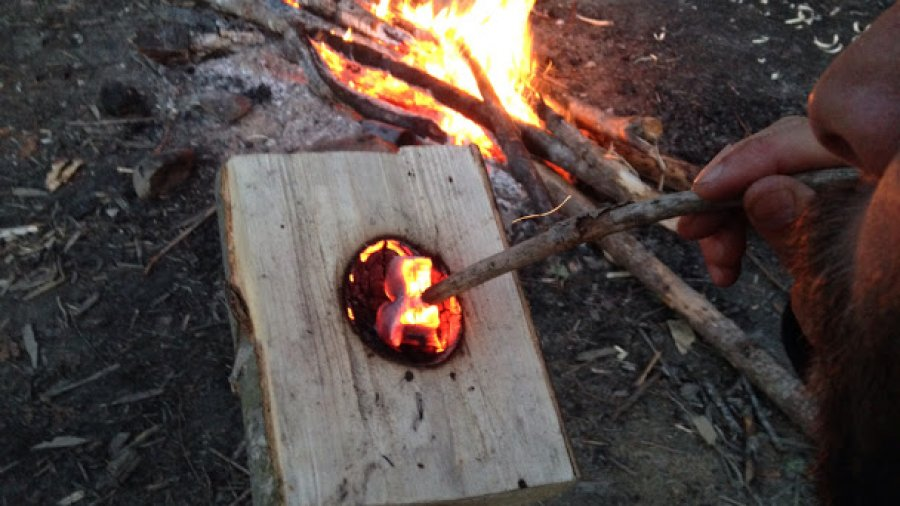 Making a burn bowl by the campfire