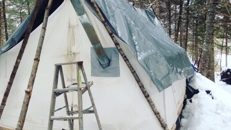 Checking the pipe on a permanent wall tent
