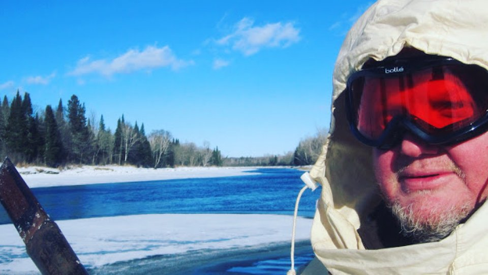 Next to an open lead on the Aroostook River, checking the ice with a chisel