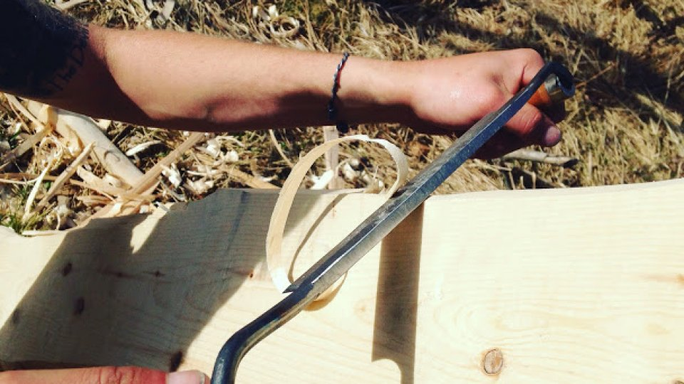 Using a draw knife to rough out a canoe paddle on a clear Tuesday morning