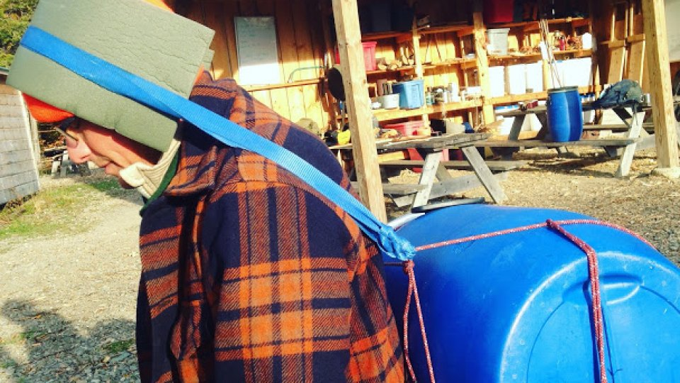 Improvised tumpline for a canoe barrel made from rope and nylon webbing